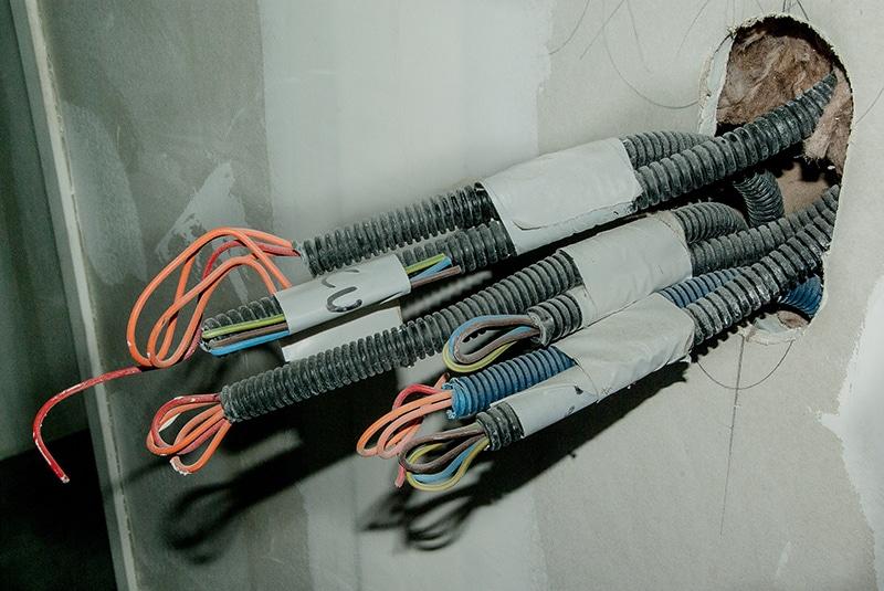 Des cables passés dans un mur pour faire passer la fibre